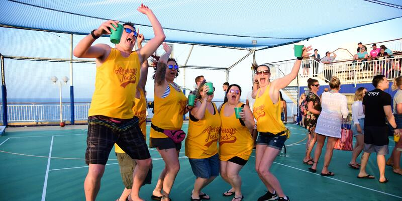 Flip cup tournament team jumping and smiling in matching shirts on Impractical Jokers Cruise 4