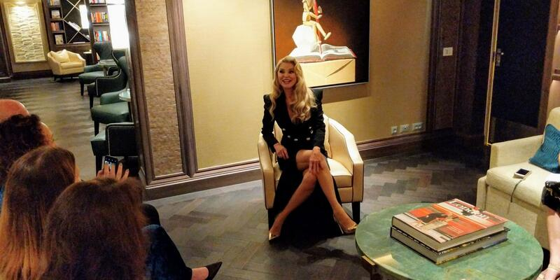 Godmother Christie Brinkley speaks with journalists in the library onboard Seven Seas Splendor