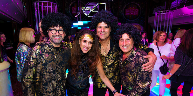 Four adult passengers dressed up in disco attire and costumes on the Ultimate Disco Cruise