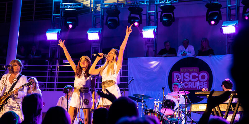 ABBA tribute band singing onstage on the Ultimate Disco Cruise