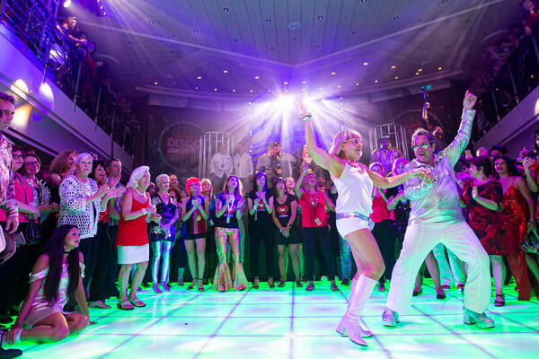 Passengers dancing in costumes in the club on the Ultimate Disco Cruise