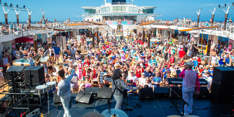 View of the crowd from the stage during a daytime concert on the pool deck during the Ultimate Disco Cruise