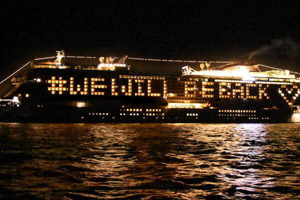 Sky Princess at sea at night, with a #WeWillBeBack message spelled out by its lit-up balcony cabins