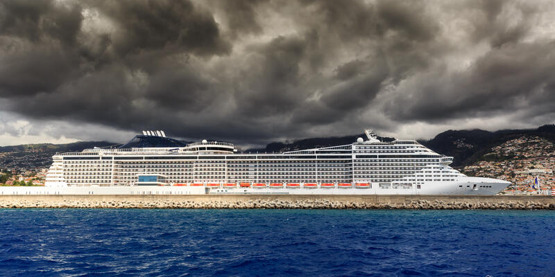 Beautiful view of the harbor of Funchal, Madeira, seen from the Atlantic ocean, with ominous clouds and a cruise ship