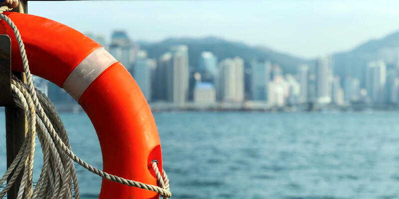 Close-up of a Life preserver ring onboard a cruise ship, with port city in the background