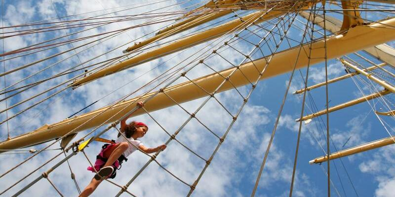 Shot of woman climbing up the mast of Star Clipper