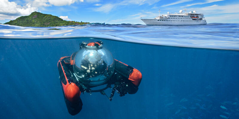 Underwater shot of Crystal Esprit's submarine, with ship on the water in the distance