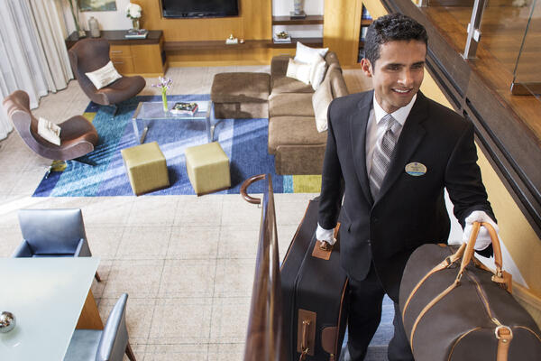 Royal Genie butler helping guests check in to a Royal Caribbean Loft Suite (Photo: Royal Caribbean)