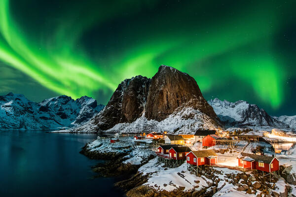 Panoramic shot of The Northern Lights over a small mountain town in Norway