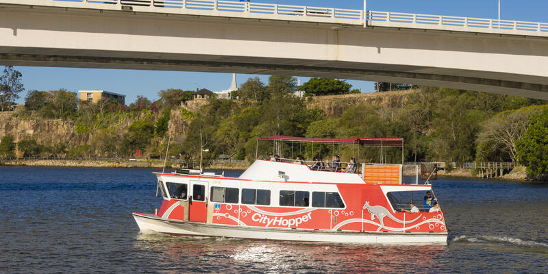 People onboard the free CityHopper ferry in Brisbane during daytime. The ferry service is free and runs along the Brisbane River.