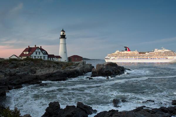 Carnival Splendor cruise ship sails past Portland Head Lighthouse. Fall is peak cruise ship season for New England, due to seasonable weather and fall foliage.
