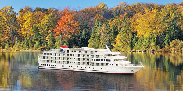 Exterior shot of American Constitution anchored along the river during fall foliage season