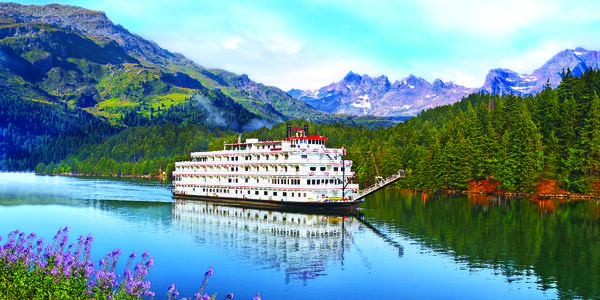Exterior shot of American Pride cruising down a scenic river with blooming flowers and mountains
