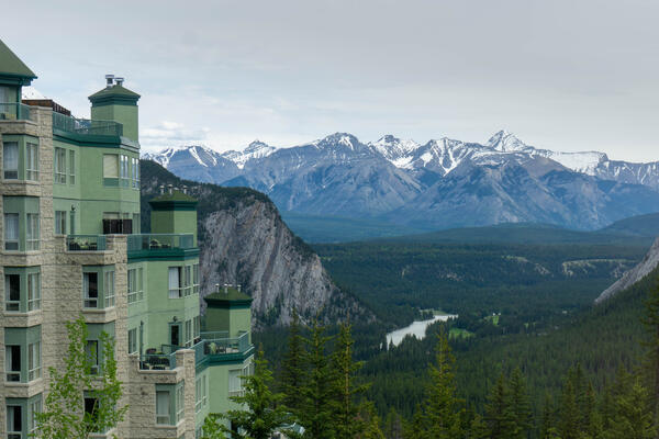 Exterior shot of The Rimrock Resort Hotel with the Canadian Rocky Mountains backdrop