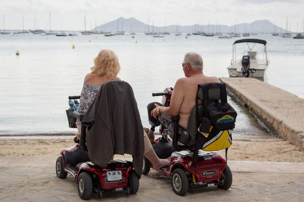 Senior couple on mobility scooters (Photo: The Art of Pics/Shutterstock)