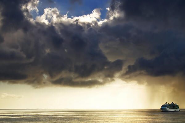 Cruise ship on the open water with dark omnious clouds looming overhead (Photo: 7489248533/Shutterstock)