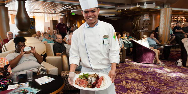 Smiling chef holding a plate of food during a Cooking Demo on Grandeur of the Seas