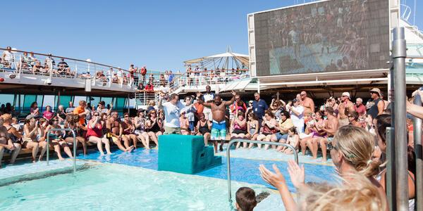 Passengers hanging around the Main Pool on Grandeur of the Seas